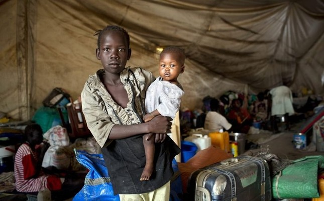 A young girl, displaced by recent fighting, holding her baby brother in a tent on the UN base in what is now home to 16,000 people in Malakal, South Sudan, 30 March 2014. (EPA Photo)