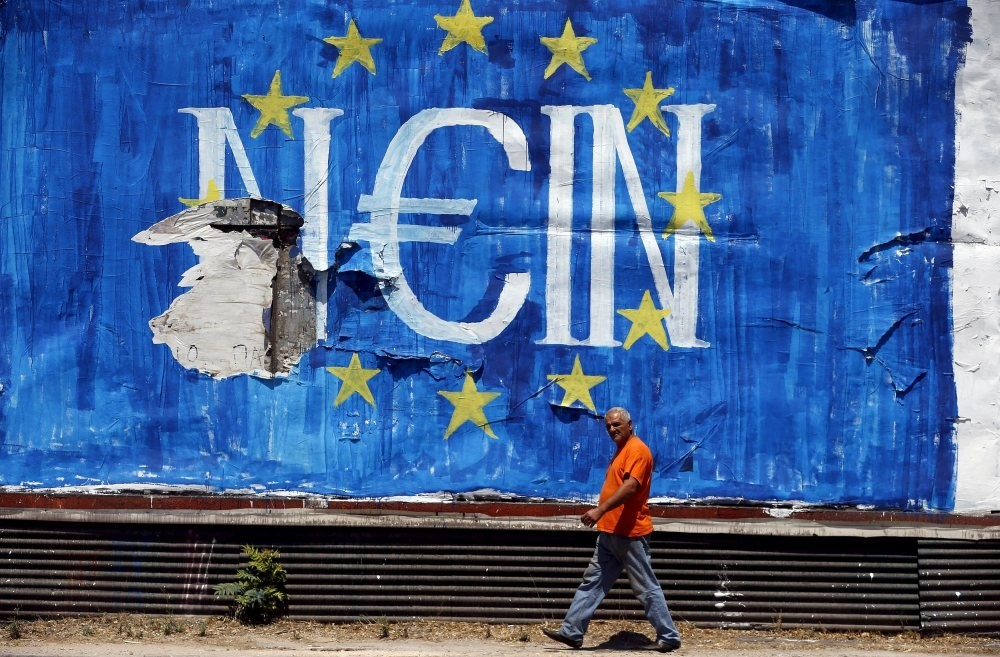 A man walks past graffiti in Athens amid discussions on whether to keep Greece in the eurozone or not. The Greek situation is likely to become another crisis in the EU in the near future.