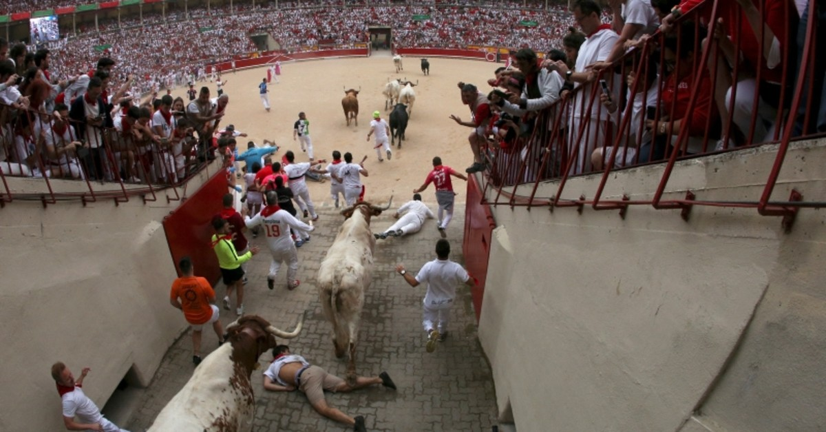 Revelers fall as they enter the bullring following the first running of the bulls at the San Fermin festival in Pamplona, Spain, July 7, 2019. (Reuters Photo)