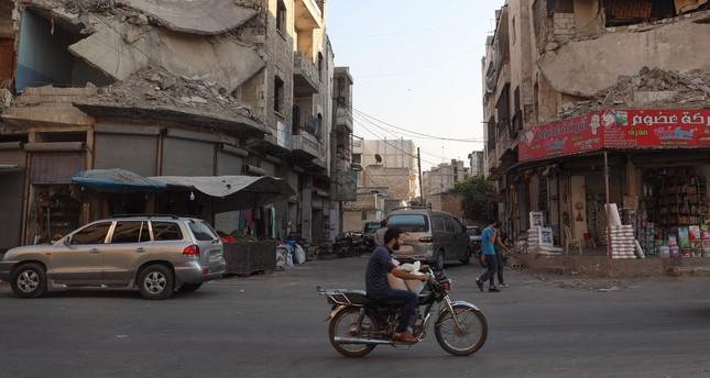 People walk near heavily damaged buildings in Idlib, northwestern Syria, Sept. 16, 2019.