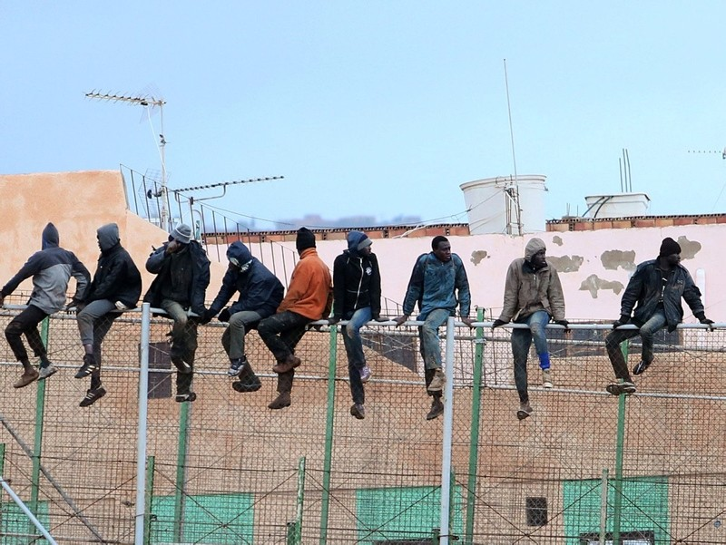 In this file photo taken on February 19, 2015 migrants sit atop a border fence separating Morocco from the north African Spanish enclave of Melilla in the first attempt to jump since the camp on Mount Gurugu burned down. (AFP Photo)