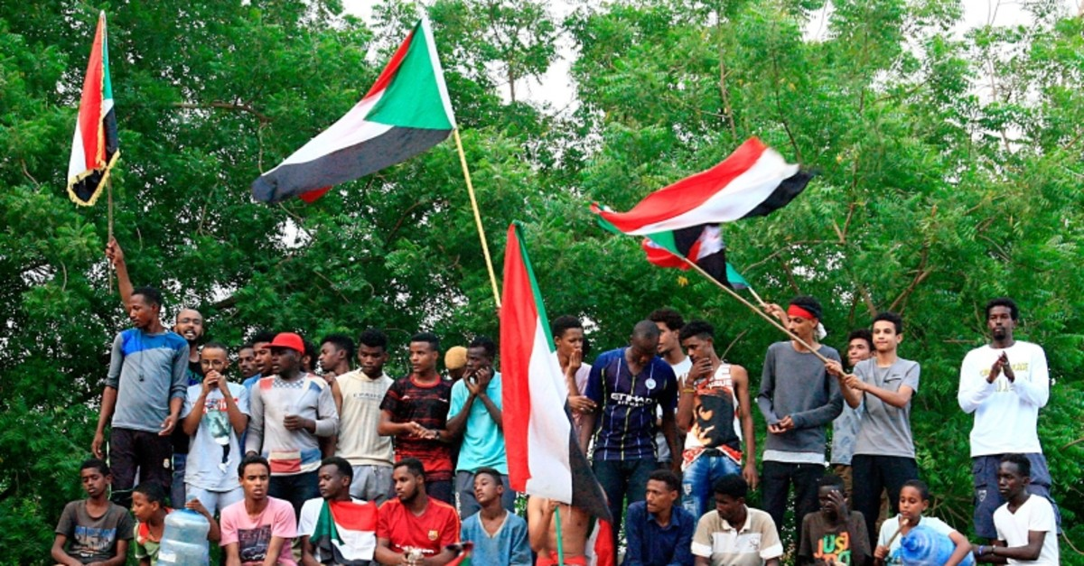 Sudanese demonstrators wave their national flag as they celebrate in Khartoum early on August 3, 2019, after Sudan's ruling generals and protest leaders reached a ,full agreement, on the constitutional declaration. (AFP Photo)