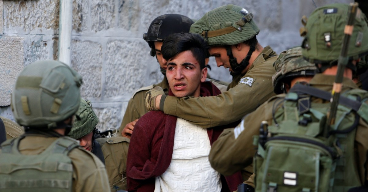 Israeli soldiers detain a Palestinian in the West Bank city of Hebron, Dec. 10, 2017.
