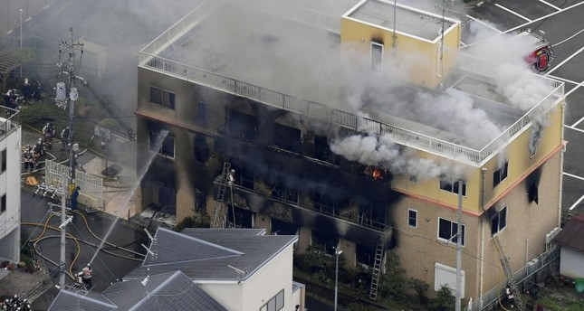 An aerial view shows firefighters battling fires at the site where a man started a fire after spraying a liquid at a three-story studio of Kyoto Animation Co. in Kyoto, Japan, July 18, 2019. AP Photo