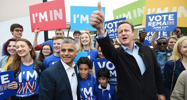 British Prime Minister David Cameron (R) and Mayor of London Sadiq Khan (L) greet supporters during the launch of the battle bus for the 'Remain In' campaign (EPA Photo)