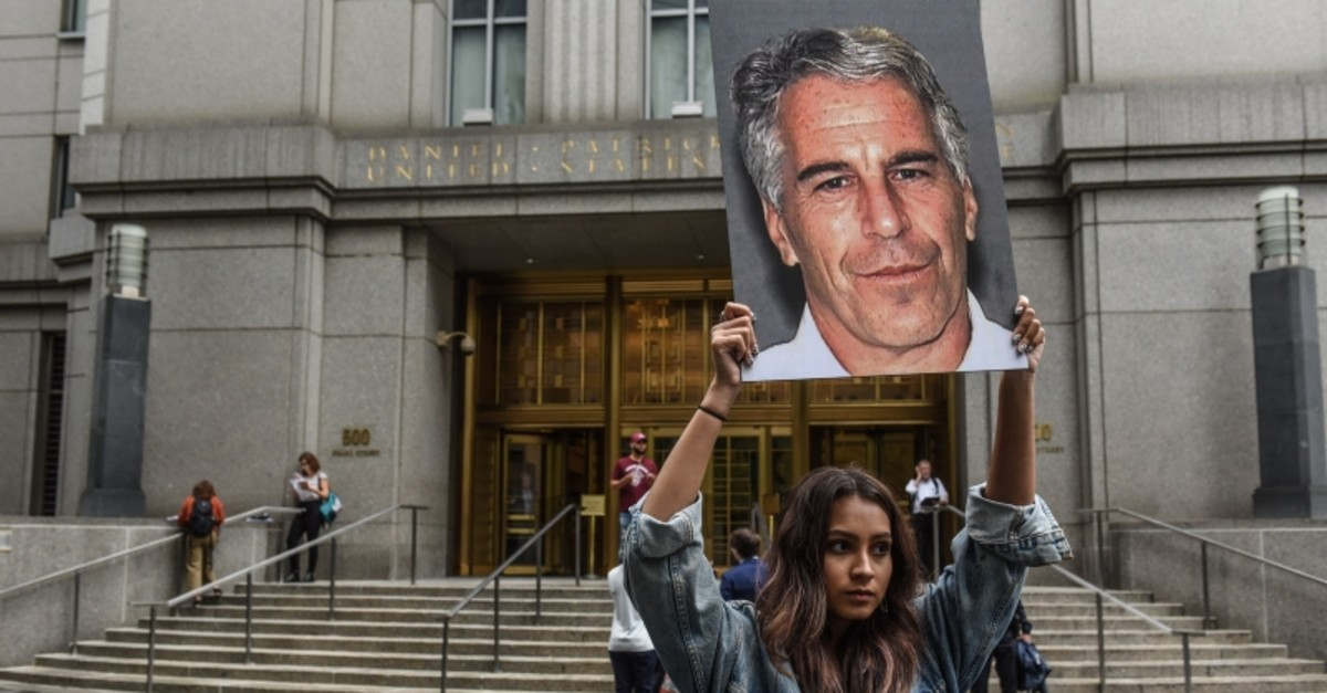 A protest group called ,Hot Mess, hold up signs of Jeffrey Epstein in front of the federal courthouse on July 8, 2019 in New York City. (AFP Photo)