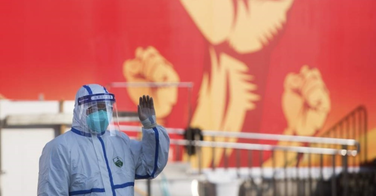 In this photo released by Xinhua News Agency, a medical worker waves near a propaganda poster as patients arrive at a temporary hospital with 1100 beds converted from the Wuhan Sports Center in Wuhan in central China's Hubei Province, Feb. 12, 2020. (Xinhua via AP)