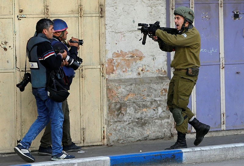 An Israeli soldier shouts as he aims his weapon during clashes with Palestinian demonstrators at a protest against U.S. decision to recognize Jerusalem as the capital of Israel, in the West Bank city of Hebron Dec. 15, 2017 (Reuters Photo)