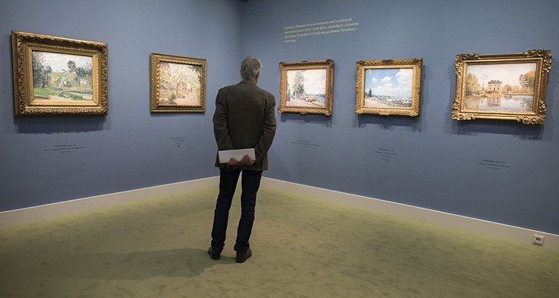 A visitor looks at paintings as part of the 'Secret Garden of the Hansens: The Ordrupgaard Collection' exhibition held at the Jacquemart-Andre museum in Paris (EPA Photo)