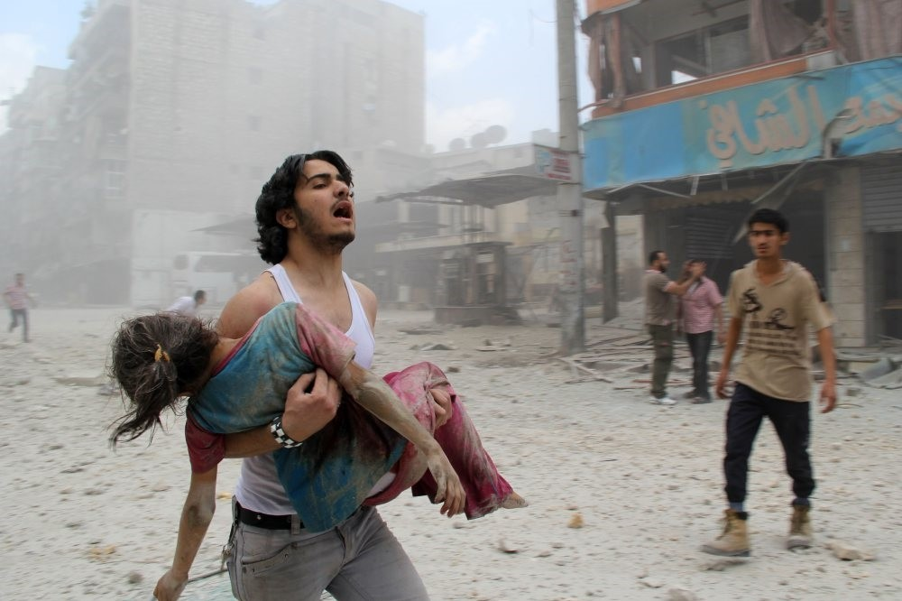 A man carrying a young girl injured in a reported barrel-bomb attack by Assad regime forces in the Kallaseh district in Aleppo, north Syria, June 3, 2014.