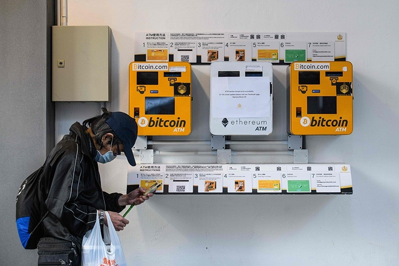 A man uses his phone as he walks past ATM machines (L and R) for digital currency Bitcoin in Hong Kong on December 18, 2017. (AFP Photo)