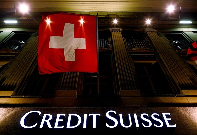 The logo of Swiss bank Credit Suisse is seen below the Swiss national flag at a building in the Federal Square in Bern, Switzerland May 15, 2014. (Reuters Photo)