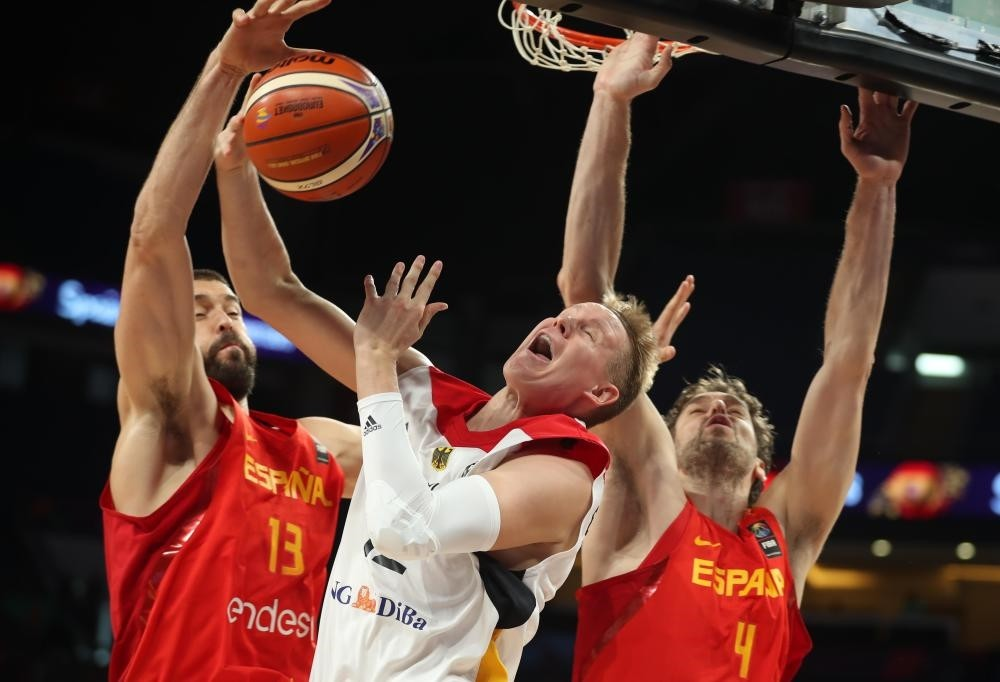 Robin Benzing of Germany and Pau Gasol and Marc Gasol of Spain in action.