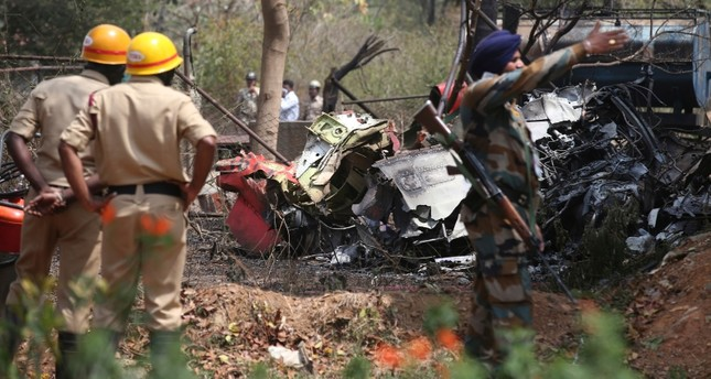 Firefighters and security officers secure the area by the wreckage after two Indian Air Force aircrafts collided midair while rehearsing for Aero India 2019 near Yelahanka air base in Bangalore, India, Feb. 19, 2019. (AP Photo)
