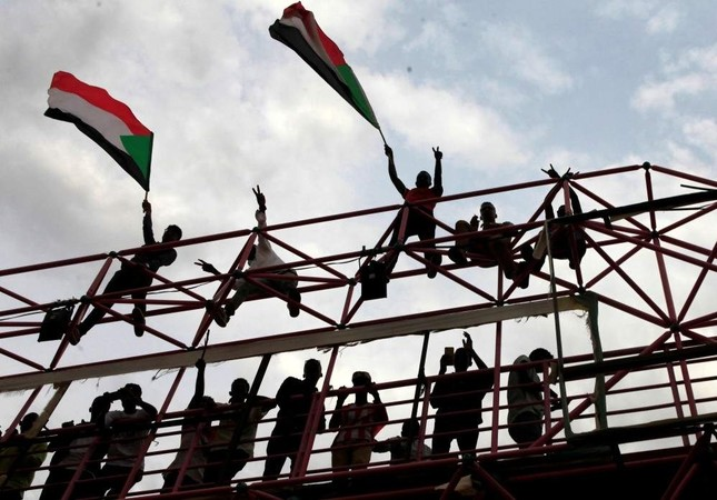 FILE PHOTO: Sudanese civilians wave their national flags during celebrations of the signing of the Sudan's power sharing deal, that paves the way for a transitional government, and eventually elections, following the overthrow of long-time leader Omar al-Bashir in Khartoum, Sudan, August 17, 2019. REUTERS/Mohamed Nureldin Abdallah/File Photo