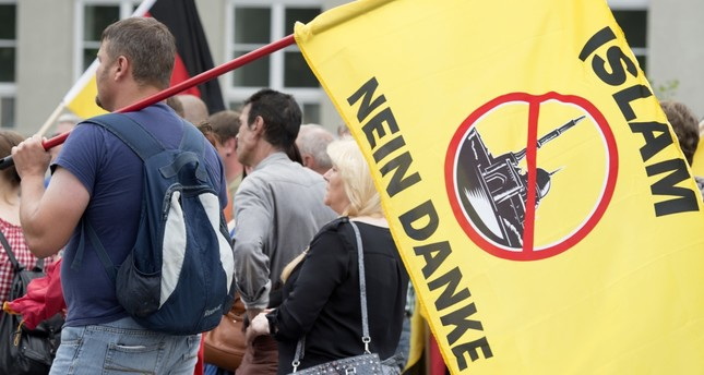 A supporter of the right-wing organization, Patriotic Europeans say No, PEsN, holding a flag reading Islam, no thanks during a rally in Erfurt, central Germany, June 4, 2016.