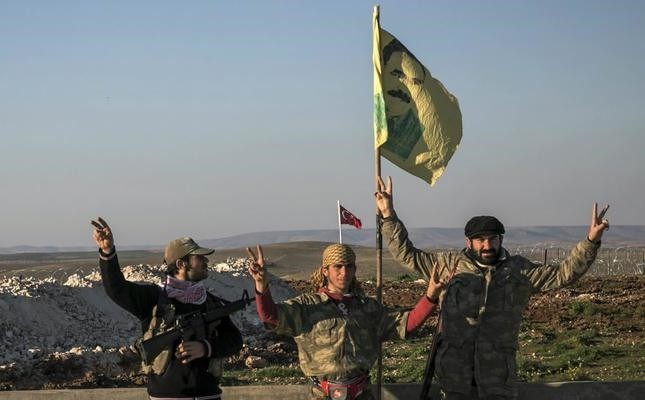 In this file photo, YPG militants are seen next to a drawing of jailed PKK leader Abdullah u00d6calan in Esme village of Aleppo province, Syria.