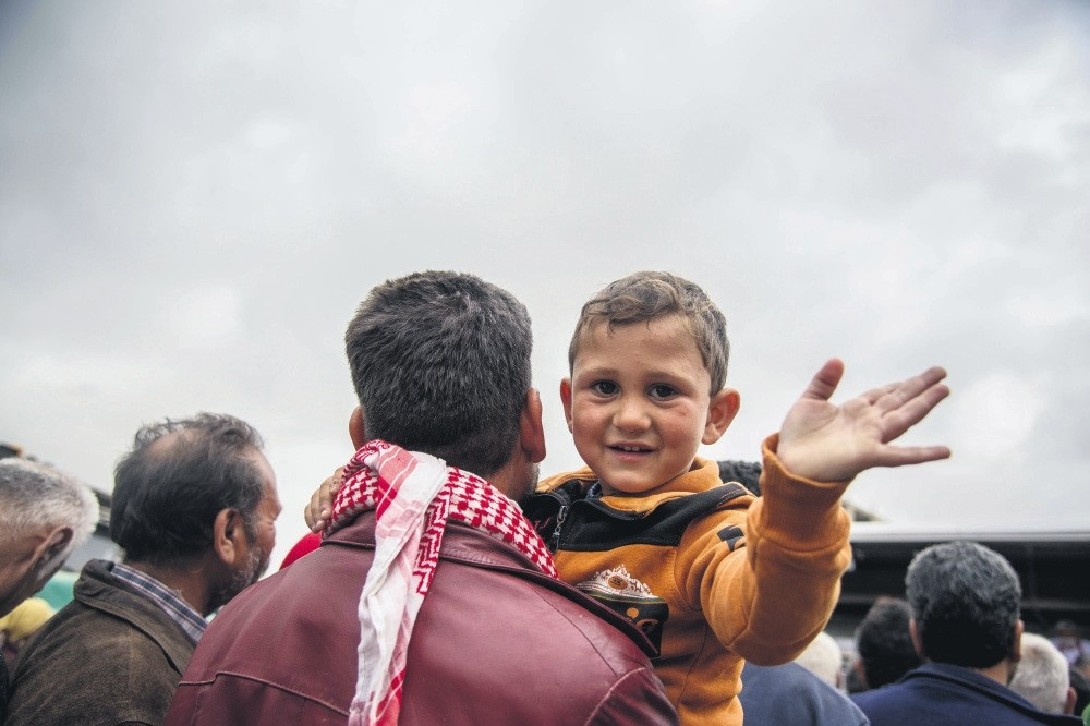 A child waves to the camera in Afrin after the city was liberated by the Free Syrian Army (FSA) backed by Turkish Armed Forces (TSK) in Operation Olive Branch.