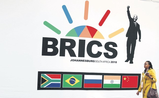 A delegate walks past a BRICS logo ahead of the 10th BRICS Summit, in Sandton, South Africa, July 24, 2018.