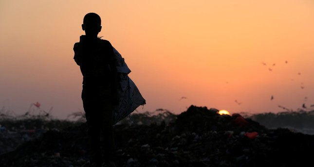 A Yemeni boy stands in a garbage dump where he collects recyclables and food near the Red Sea port city of Hodeidah, Yemen. (Reuters Photo)