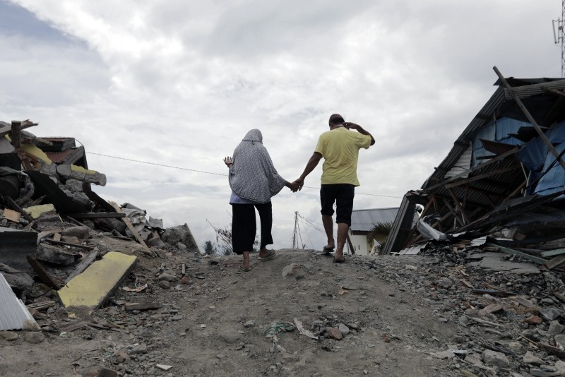 Residents of Balaroa walk through the ruins of a house in an earthquake devastated area at Balaroa village, in Palu, Central Sulawesi, October 11, 2018. (EPA Photo)