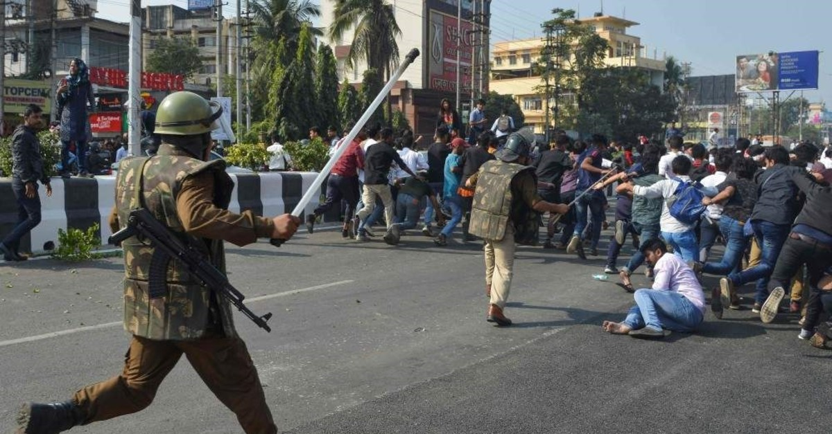 Security personnel use batons to disperse students protesting against the citizenship bill, Guwahati, Dec. 11, 2019. (AFP Photo)