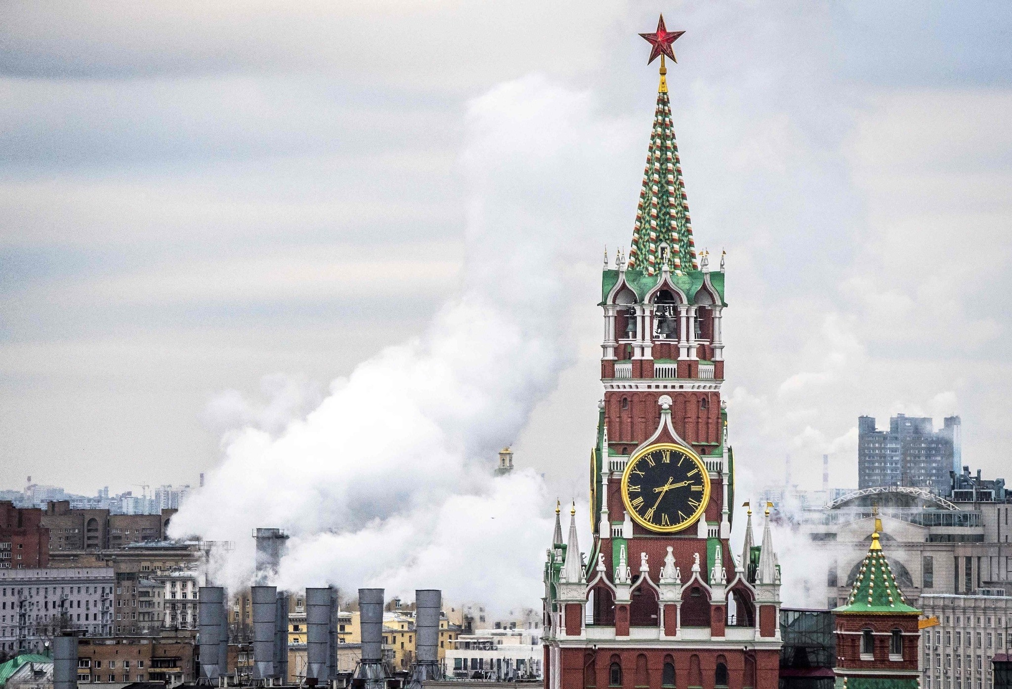 The Kremlinu2019s Spasskaya Tower and a heating power plant in Moscow.