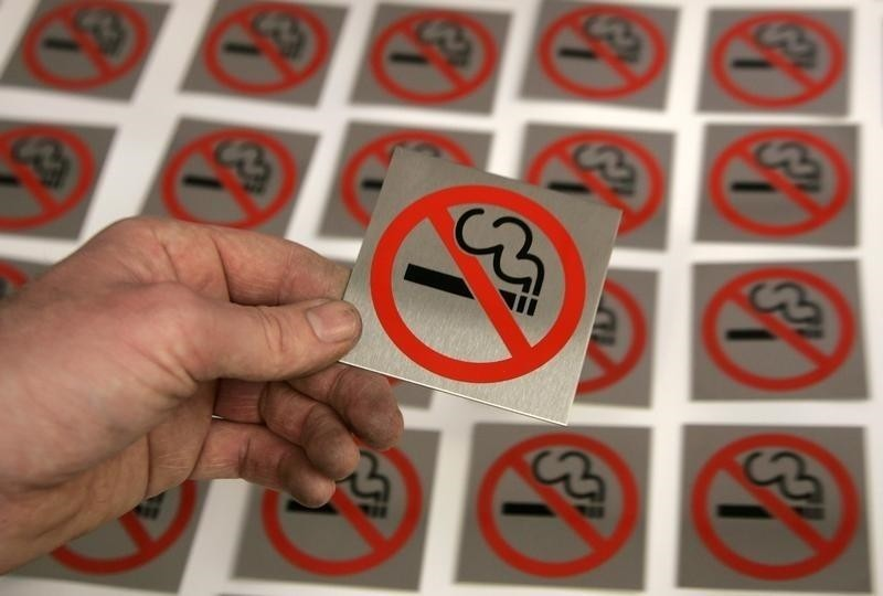 A printer lays a no smoking sign alongside others at First Safety Signs in Bishops Stortford (Reuters File Photo)