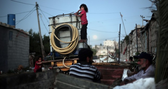 Palestinian children climb on a portable tank used to distribute water in el-Zohor slum, on the outskirts of Khan Younis refugee camp, southern Gaza Strip.