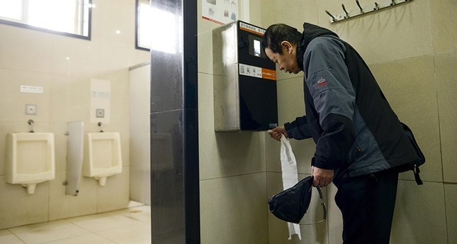 A man uses an automatic toilet paper dispenser that uses facial recognition technology at a public toilet at the Temple of Heaven in Beijing on March 21, 2017. (AFP Photo)