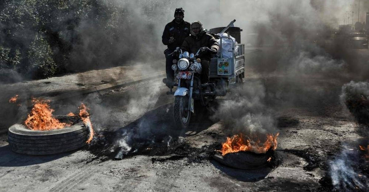 A motorcycle cart is seen before flaming tyres at a make-shift roadblock along the road leading to Najaf International Airport in the central Iraqi holy shrine city on Jan. 26, 2020. (Photo by Haidar HAMDANI / AFP)