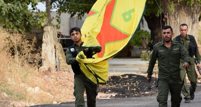 YPG terrorists walk carrying a People's Protection Units (YPG) yellow flag in the Syrian town of Ain al-Arab, along the border with Turkey in the north of Aleppo governorate on Ocotber 18, 2019. (AFP Photo)