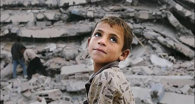 A boy stands  in front of a destroyed building after the earthquake, which killed thousands of people.