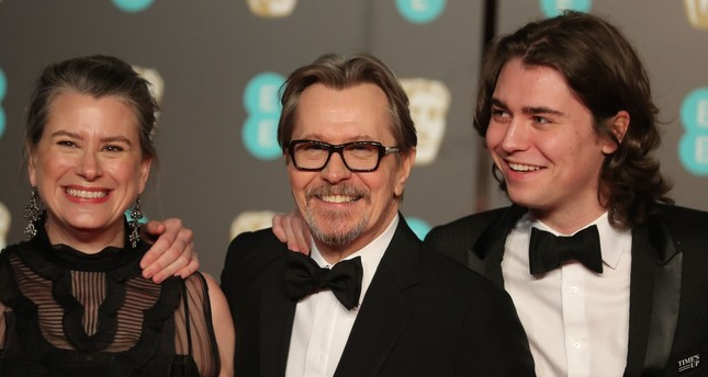 British actor Gary Oldman (C) and family pose on the red carpet upon arrival at the BAFTA British Academy Film Awards at the Royal Albert Hall in London on February 18, 2018. (AFP PHOTO)