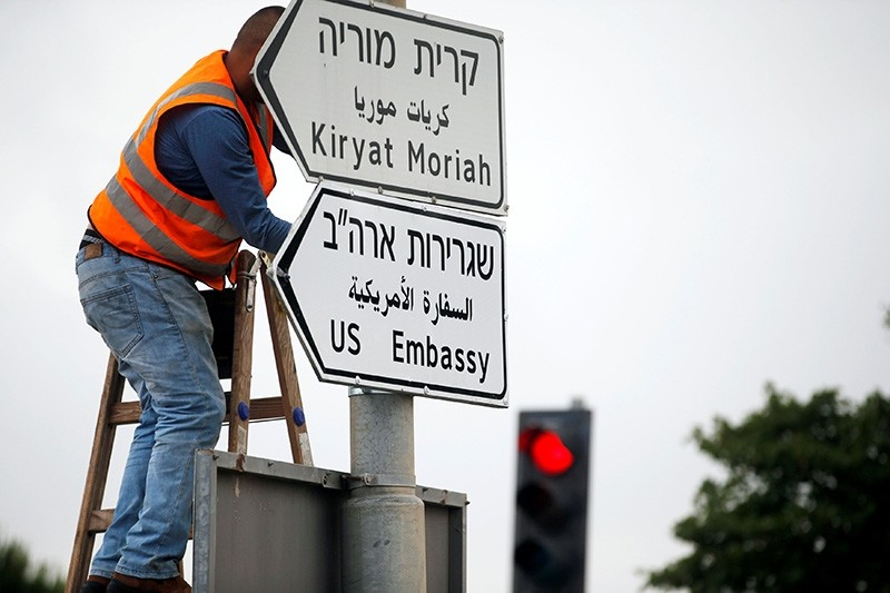 A worker hangs a road sign directing to the U.S. embassy, in the area of the U.S. consulate in Jerusalem, May 7, 2018. (Reuters Photo)