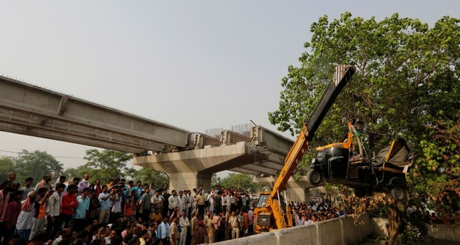 A crane is used to lift an auto rickshaw that got crushed after a highway overpass being built collapsed in Varanasi, India, Wednesday, May 16, 2018 (AP Photo)