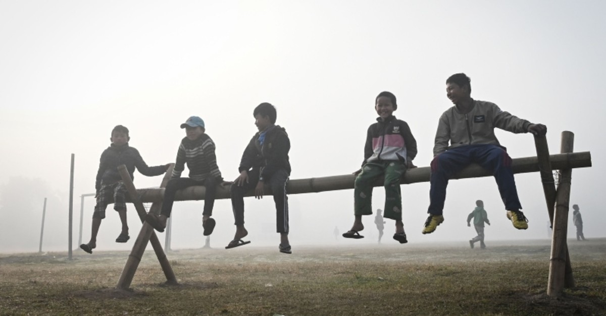 This Feb. 12, 2020, photo shows children sitting on a makeshift bench as they play in Hkamti, Myanmar. (AFP Photo)