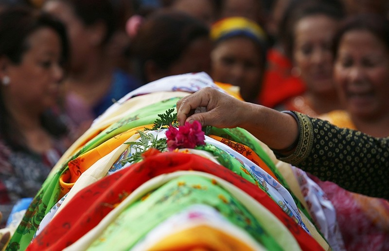 A flower is placed over the dead body of Nepalese mountaineer Min Bahadur Sherchan during his funeral in Kathmandu, Nepal. (EPA Photo)