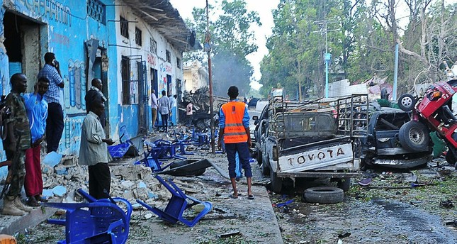 People stand among damages at the scene of a blast after two car bombs exploded in Mogadishu on October 28, 2017. (AFP Photo)