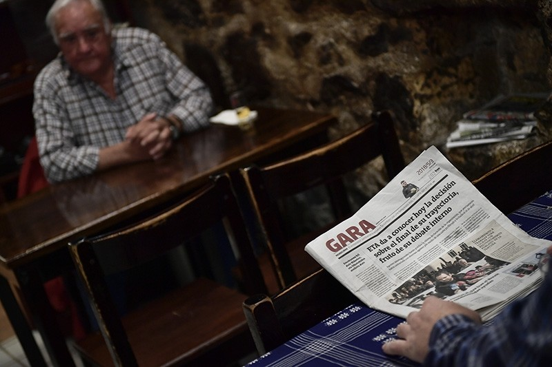 A man reads a basque nationalist newspaper reporting on the dissolution of the Basque armed separatist group ETA,  in the small basque village of Hernani, northern Spain, Thursday, May 3, 2018. (AP Photo)