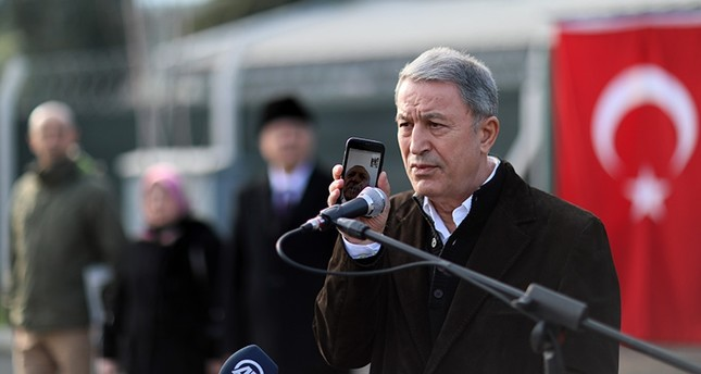 Defense Minister Hulusi Akar (R) holds a mobile phone as President Recep Tayyip Erdoğan addresses soldiers via video call at the 2nd Army Tactical Operations Center in Hatay, Turkey on Jan. 20, 2019. (AA Photo)