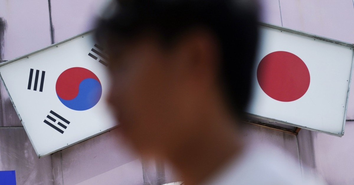 A man walks past an advertisement featuring Japanese and South Korean flags at a shop in the Shin Okubo area, known for Korean restaurants and stores selling K-pop merchandise, Tokyo, Aug. 13, 2019.