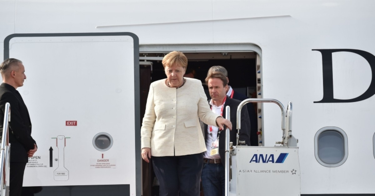 Germany's Chancellor Angela Merkel (C) arrives at at Kansai airport in Izumisano city, Osaka prefecture, on June 28, 2019 to attend the G20 Osaka Summit. (AFP Photo)