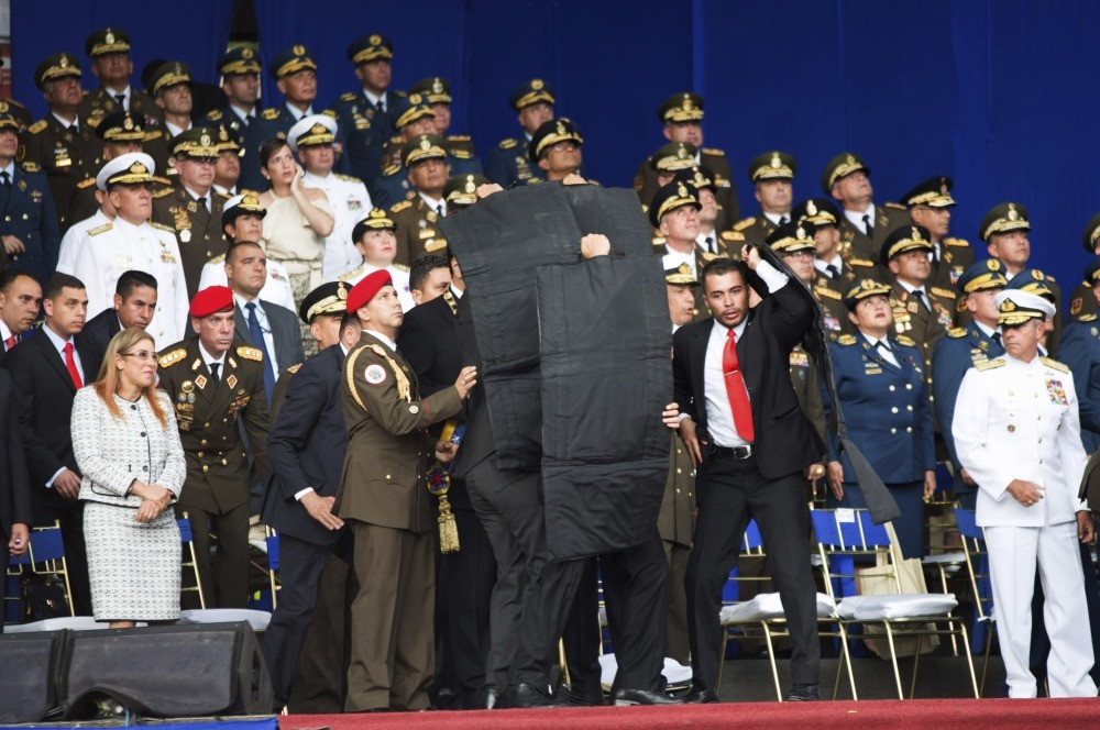 Security personnel surround Venezuela's President Nicolas Maduro after an assassination attempt made by drones armed with explosives against the president as he gave a speech in Caracas, Aug. 4.