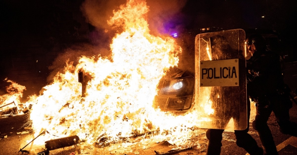 Policemen run as a police van drives over a burning barricade during clashes between protestors and police in Barcelona, Spain, Wednesday, Oct. 16, 2019. (AP Photo)