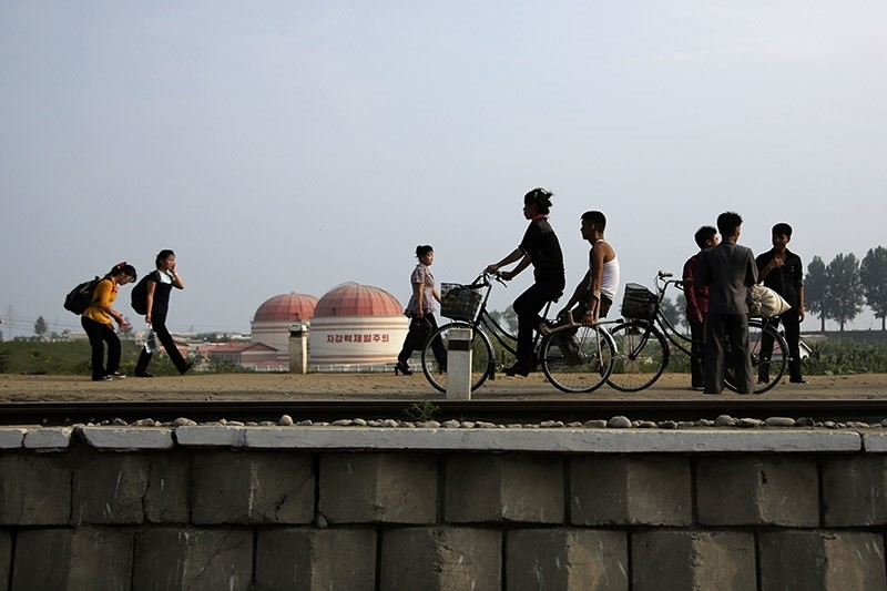 North Koreans walk while some cycle past a factory dome with Korean words painted on its side which read ,First priority: self development, at the end of a work day on Thursday, July 20, 2017, in Hamhung, North Korea. (AFP Photo)