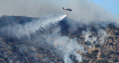 pSurging Santa Ana winds on Saturday drove an enormous wildfire toward a wealthy community in the coastal mountains northwest of Los Angeles, leaving fire crews working in a pall of...