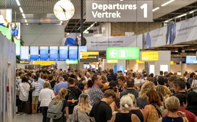 People wait in the departure hall of the Amsterdam-Schiphol airport, southwest of Amsterdam, as a problem with refuelling grounded several dozen planes and hundreds of passengers on July 24, 2019 AFP Photo