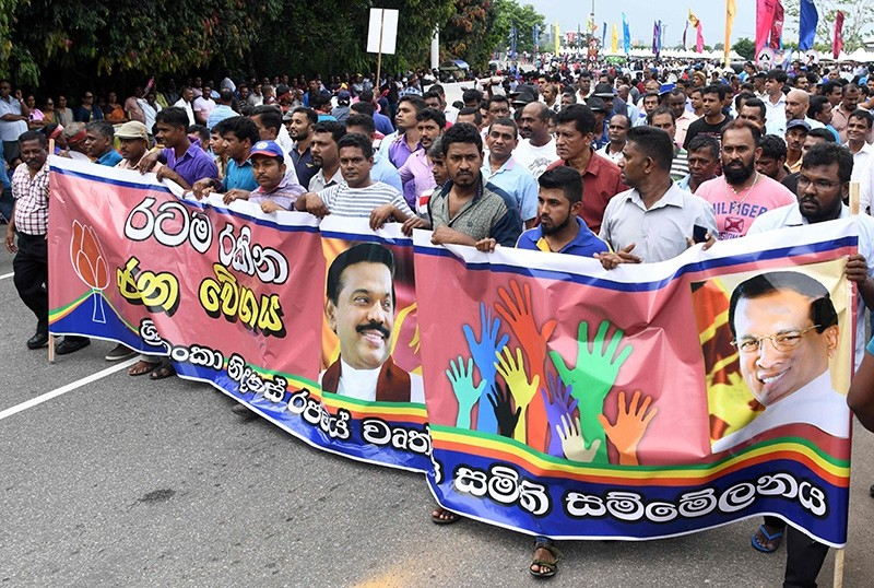 Supporters carry a banner with pictures of Sri Lanka's former president and newly appointed prime minister Mahinda Rajapakse and President Maithripala Sirisena at a rally in Colombo on Nov. 5, 2018. (AFP Photo)