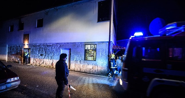 Policemen and firefighters work outside the building, in the background, where a heater exploded killing people in the village of Vila Nova da Rainha, outside Tondela, northern Portugal, in the early hours of Sunday, Jan. 14 2018. (AP Photo)